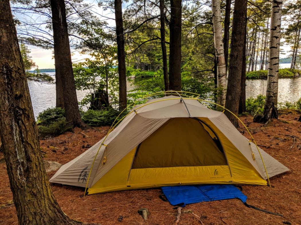 Yellow tent set up between trees on the edge of lake