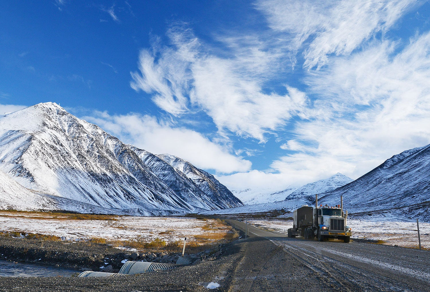 freight truck drives up a snowy dalton highway with mountains visible in the distance