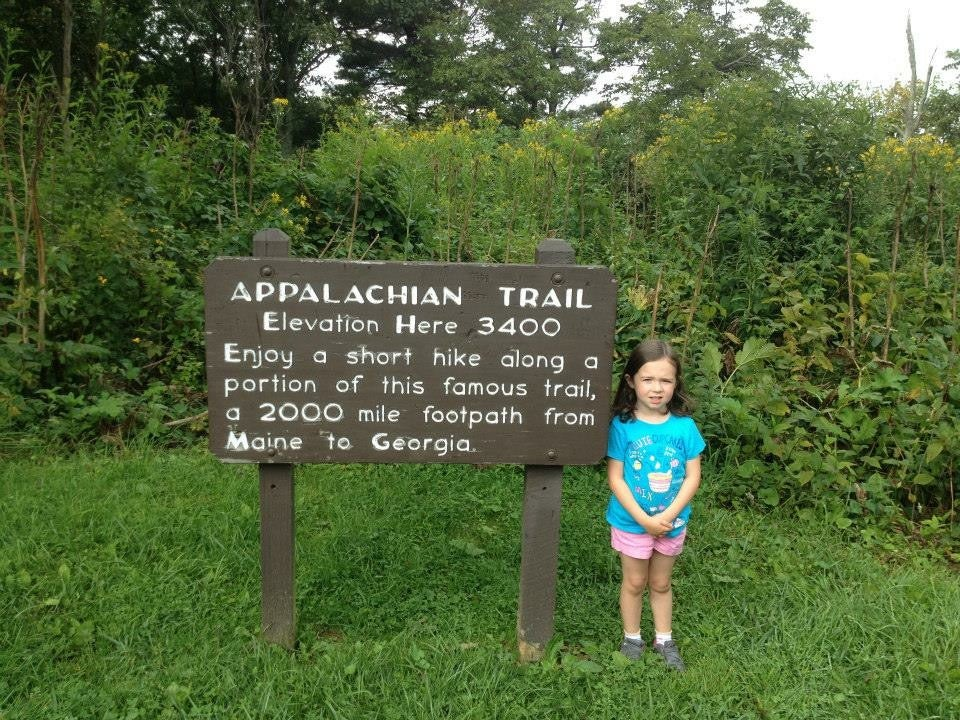 A young girl next to Appalachian Trail sign near Endless Caverns Campground