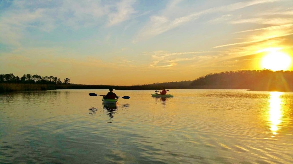 two kayakers paddling during a golden sunset