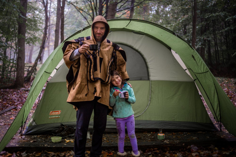 man and young girl pose in front of green tent in a wet, wooded campsite