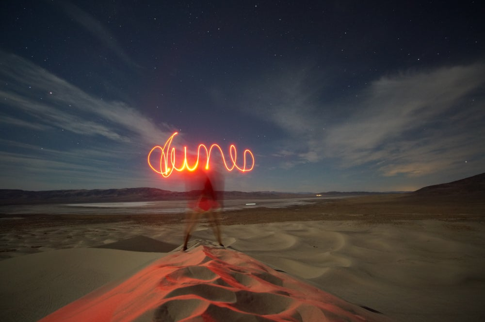 Person doing a light painting with words that say 'dunes' at dusk near Sand Mountain in Nevada