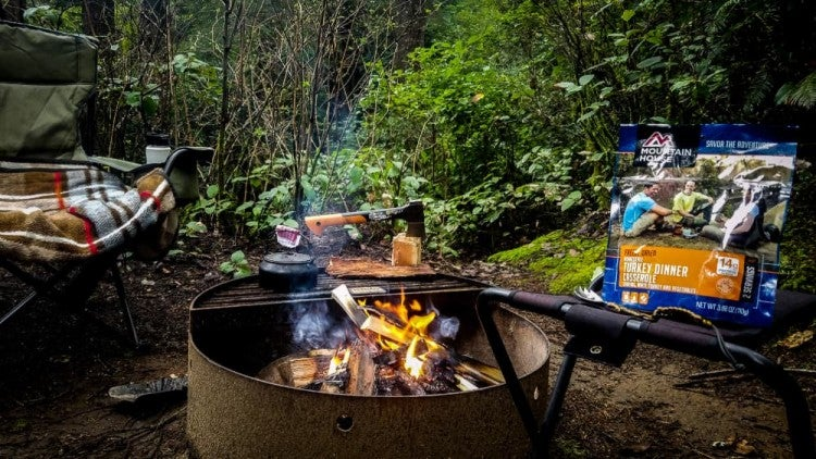 wooded campsite with lit campfire in designated ring, mountain house freeze dried meal in the background