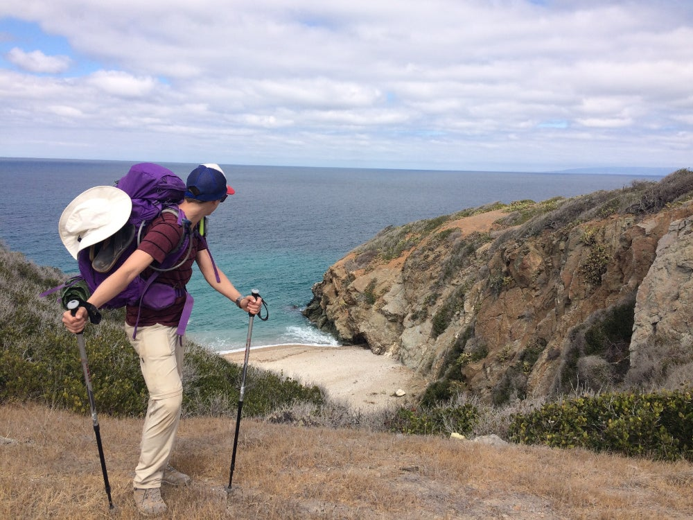 Man hiking in the foreground with a small beach in background on Parson's Landing on Catalina Island