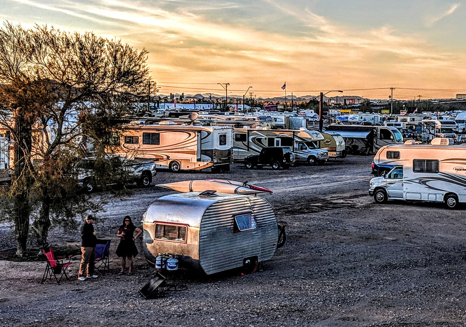 a sunset overlooking a field of RV trailers and vans at the Quartzsite, AZ RV festival in 2019