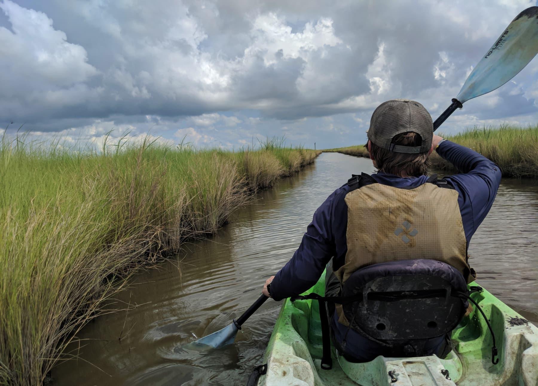 overcast sky and man paddling green kayak through marshy channel