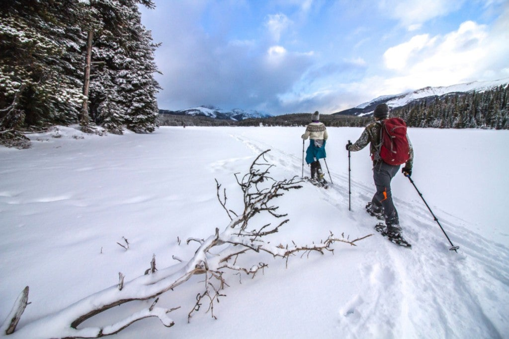 A couple wearing winter gear snowshoe onto a large snowy frozen lake with mountains in the background