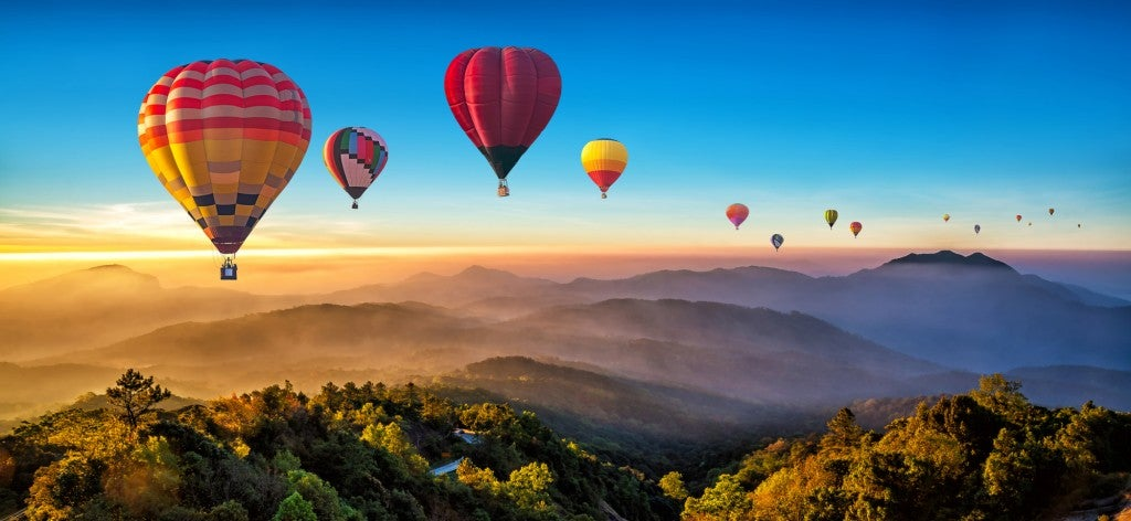 multiple hot air ballons floating above mountains at dawn