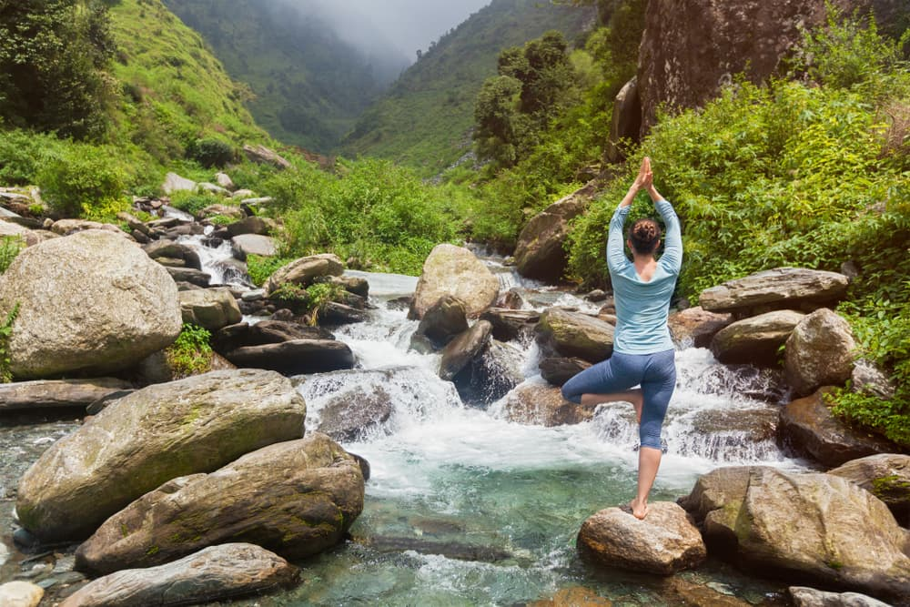 woman doing yoga pose standing on rock in mountain stream with misty mountains in the background
