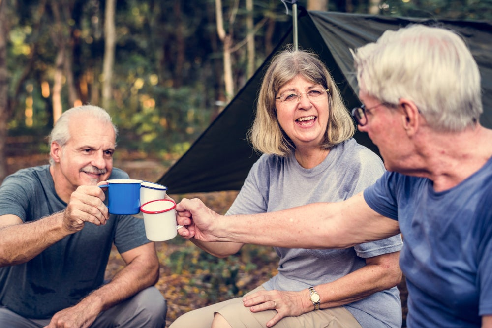 three seniors gathered in wooded campsite toasting with their mugs