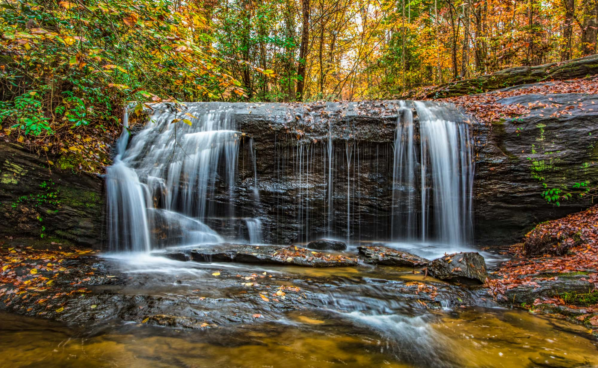 Panoramic photo of waterfall in SC with fall foliage in the background