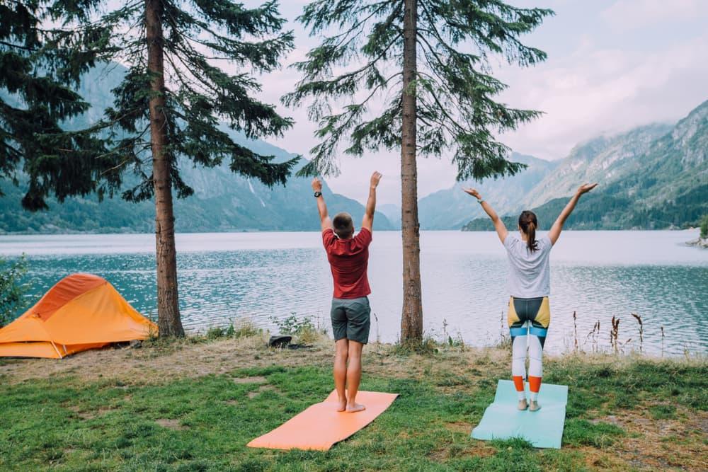 man and woman doing standing yoga pose next to orange tent overlooking mountain lake