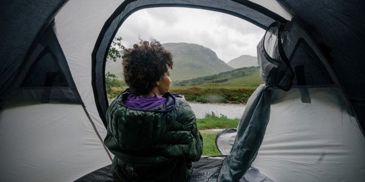 woman attempting to stay dry while gazing out at rainy hillside from inside waterproofed tent