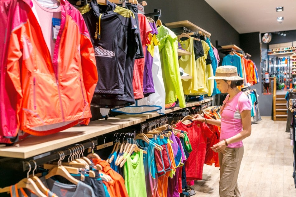 woman in straw hat shopping for jackets in an outdoor gear store