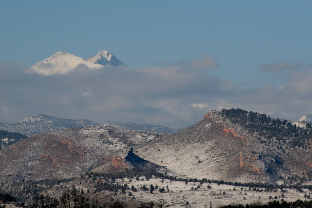 clouds hovering in blue sky over snow-frosted mountains in colorado