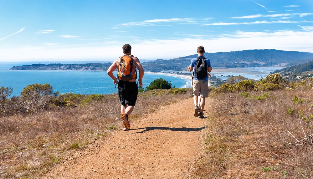 two men with backpacks running down dipsea trail toward stinson beach