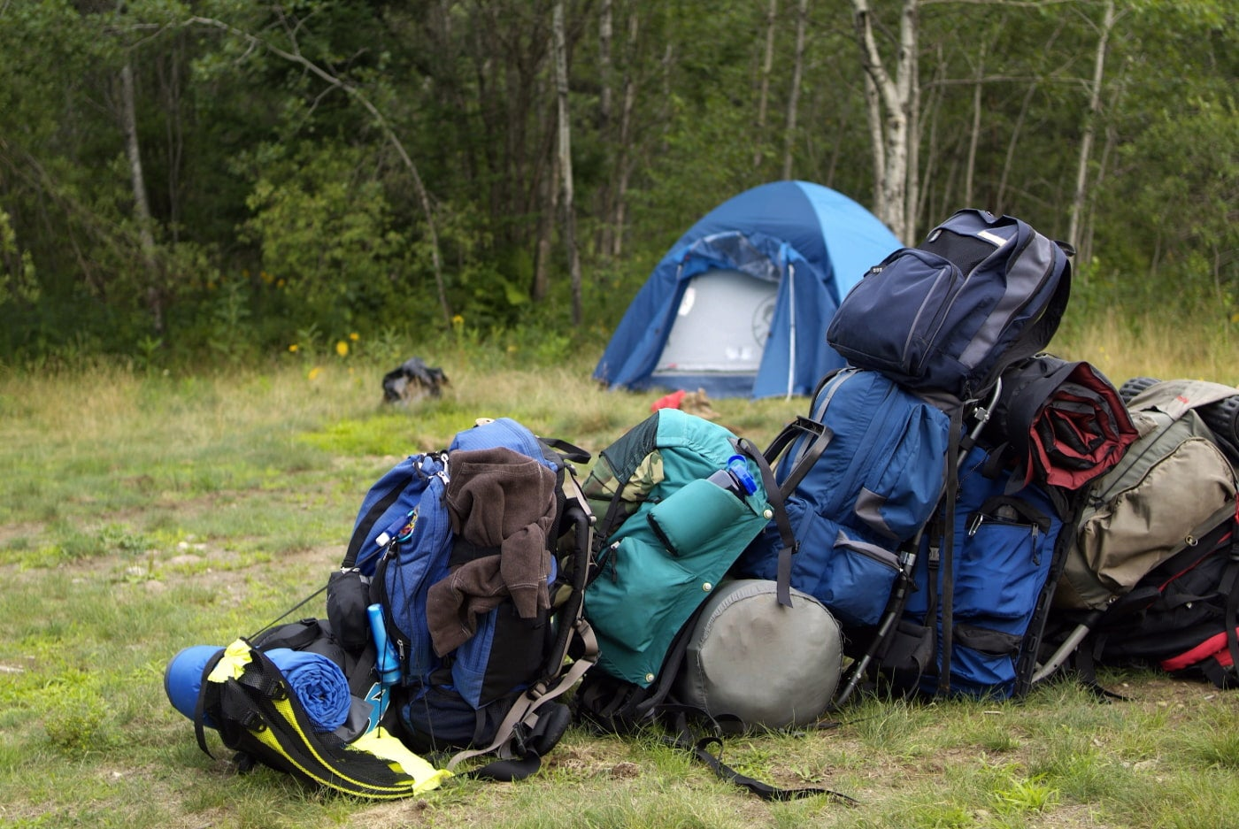 Blue and green backpacking packs stacked in a pile at a wooded tent campsite