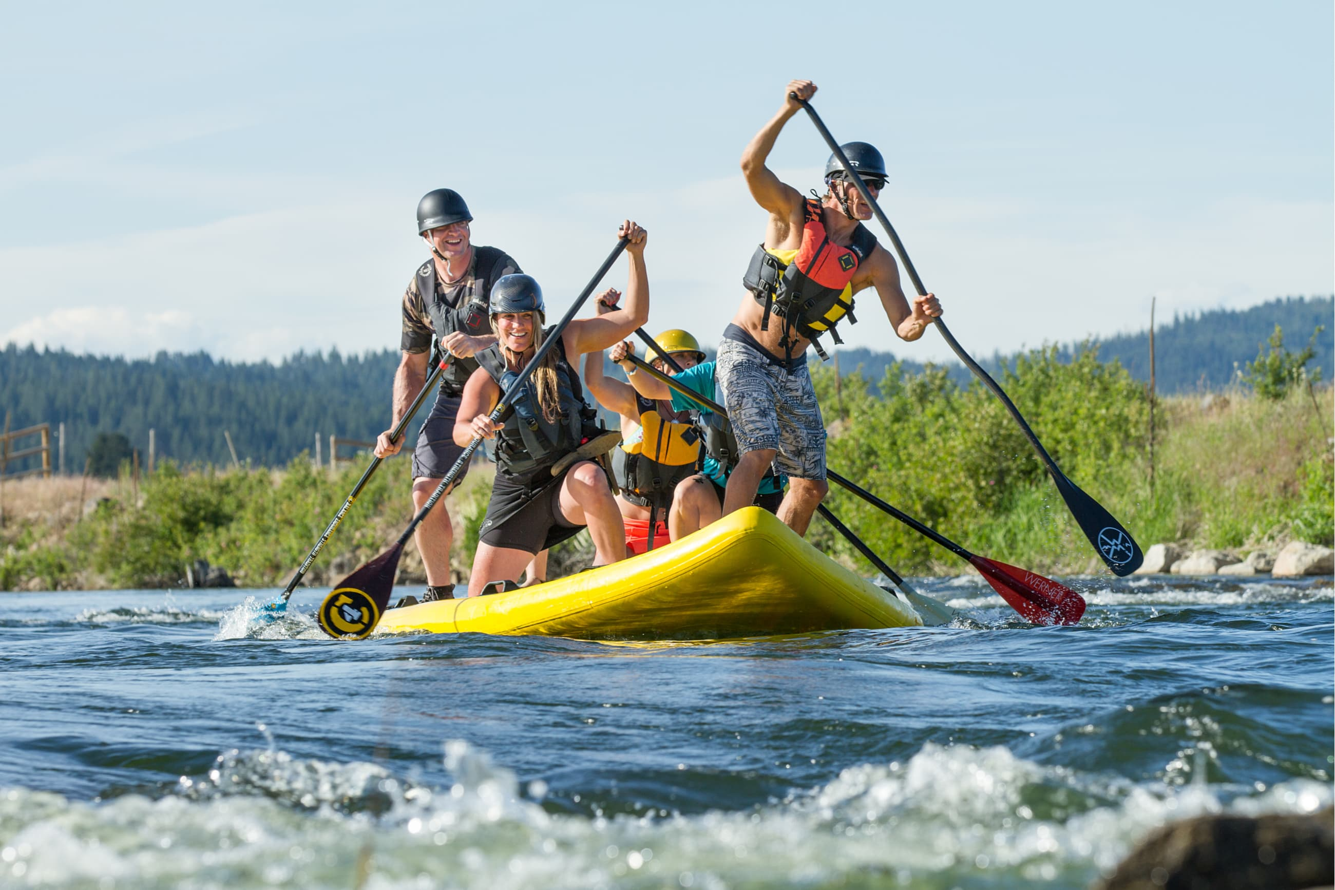 5 people on a large inflatable stand up paddle board racing down a river