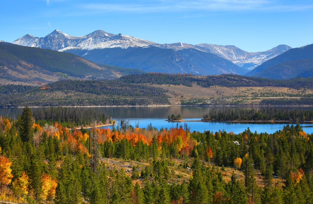 large mountains visible in the distance from alpine lake surrounded by fall foliage