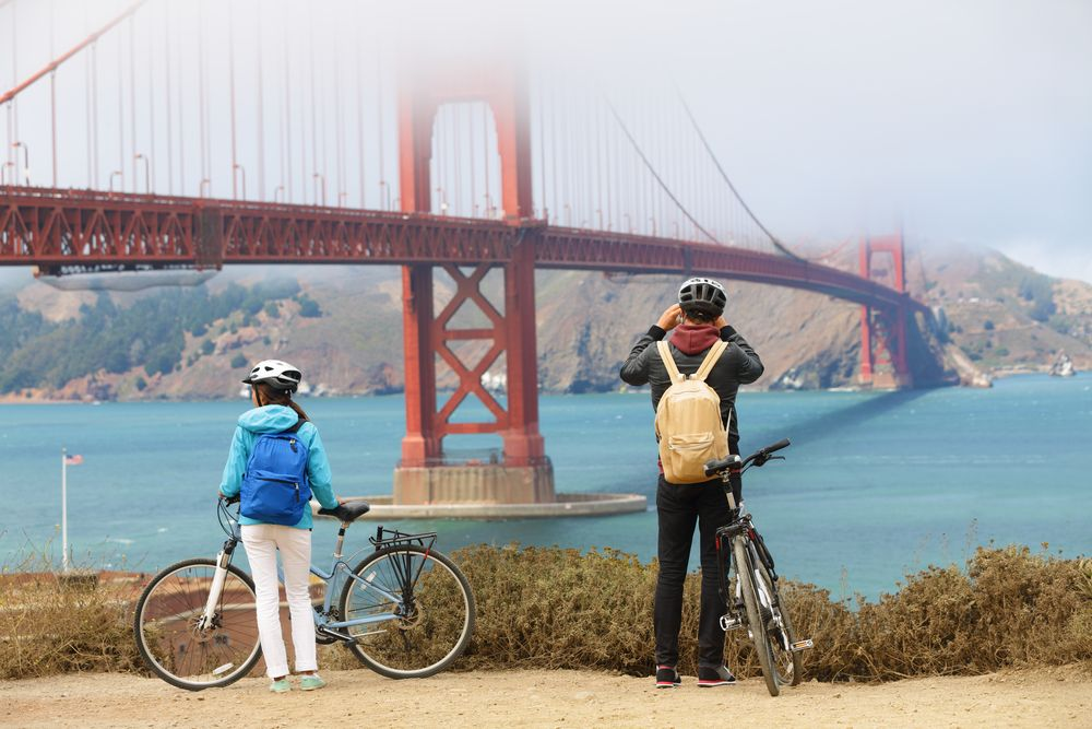 two bikers stop to take a photo of the golden gate bridge