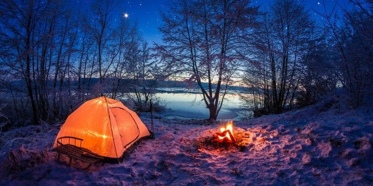 night shot of glowing orange tent and campfire in the snow on the edge of a partially frozen lake
