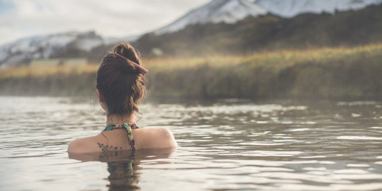woman wades in hot springs near salt lake city with snow covered mountains in the backdrop