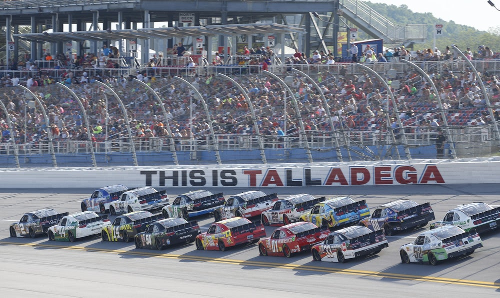"Multiple cars close together racing on NASCAR home track in Alabama. Sign on track says ""This is Talladega"""