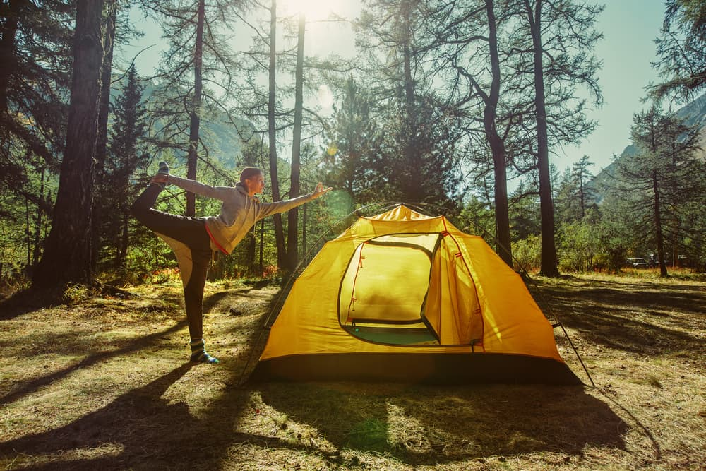 woman doing standing yoga pose next to yellow tent in the forest