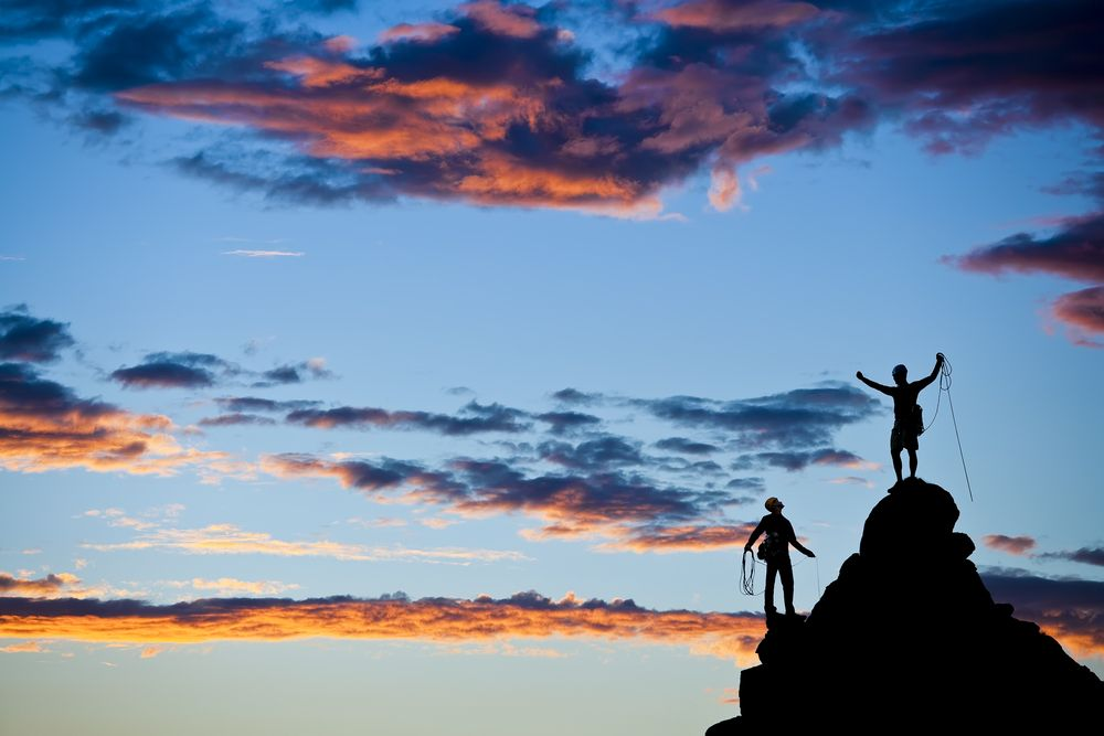 silhouette of two climbers celebrating atop a rock pinnacle