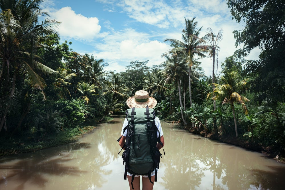 Woman with backpack standing in the middle of a river in a tropical destination