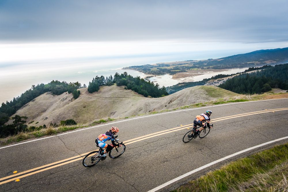 cyclists speed down hill over stinson beach