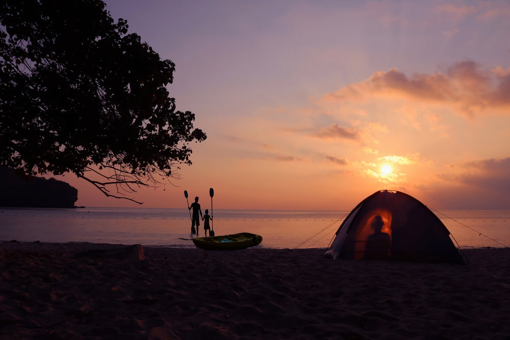 silhouette of man and child wading in beach, holding oars at sunset beside a backlit tent