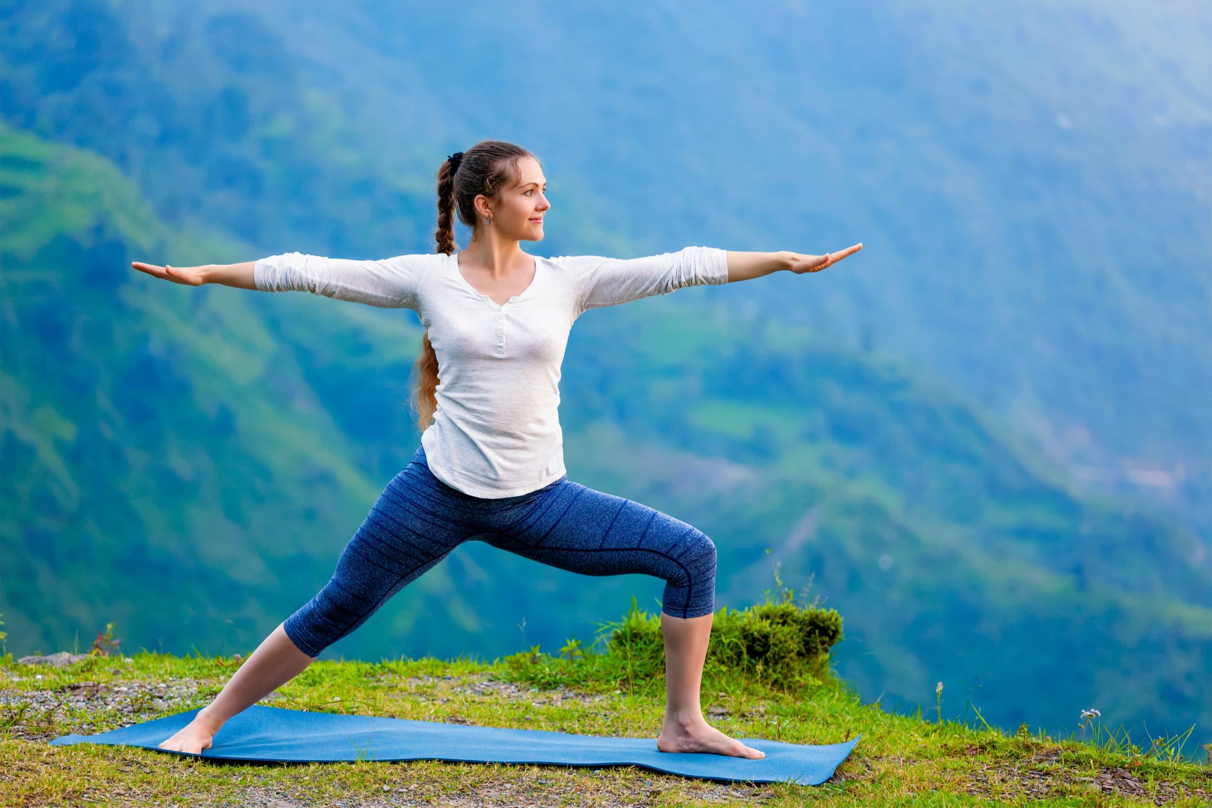 woman doing vinyasa yoga pose in the mountains