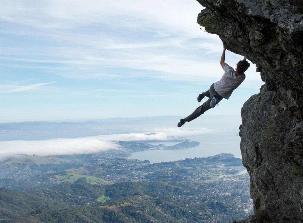 climber dangling from obermans rock over san francisco
