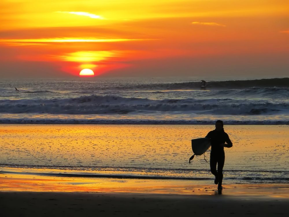 sunset at a beach in san francisco with a silhouette of a surfer in the foreground
