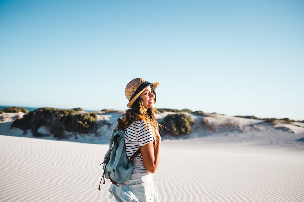 Young female smiling in front of white sandy beach dunes wearing a straw hat and backpack