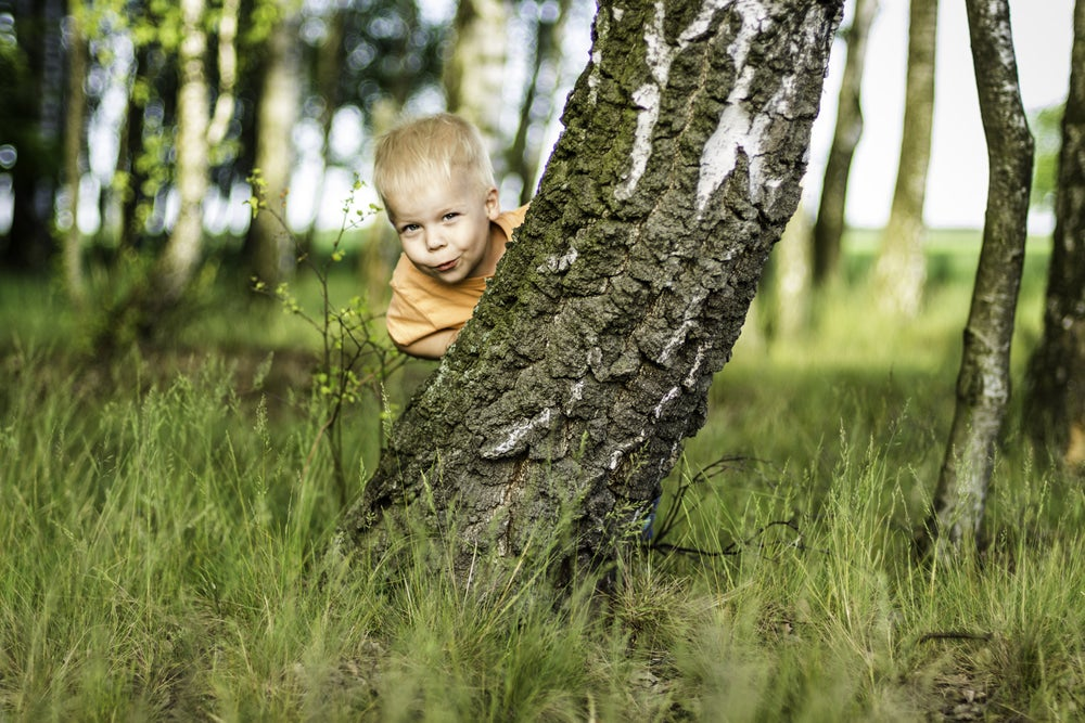 young boy peeking from behind a tree