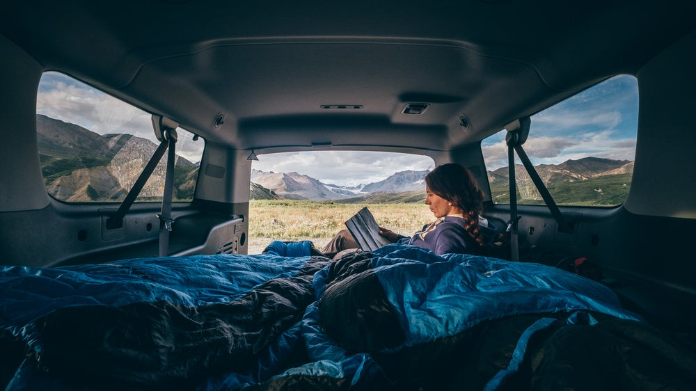 Woman reading a book in a van with mountains in the background