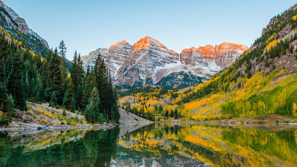 Orange alpenglow on Maroon Bells mountaintops reflect in alpine lake