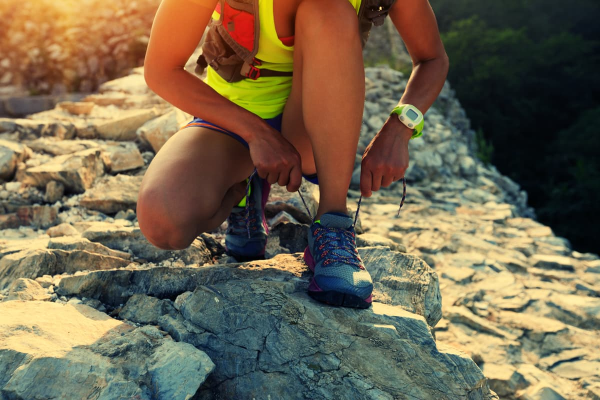 woman in yellow shirt kneeling down and tying shoe on rocky trail