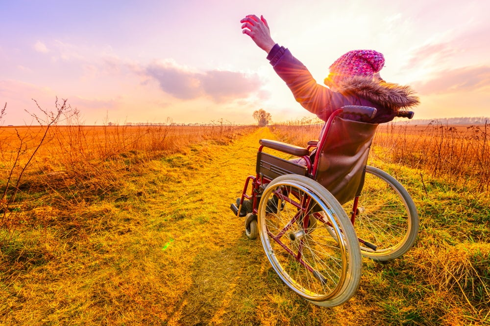 Woman with pink hat in a wheelchair holding up her arms in a celebratory fashion at sunset