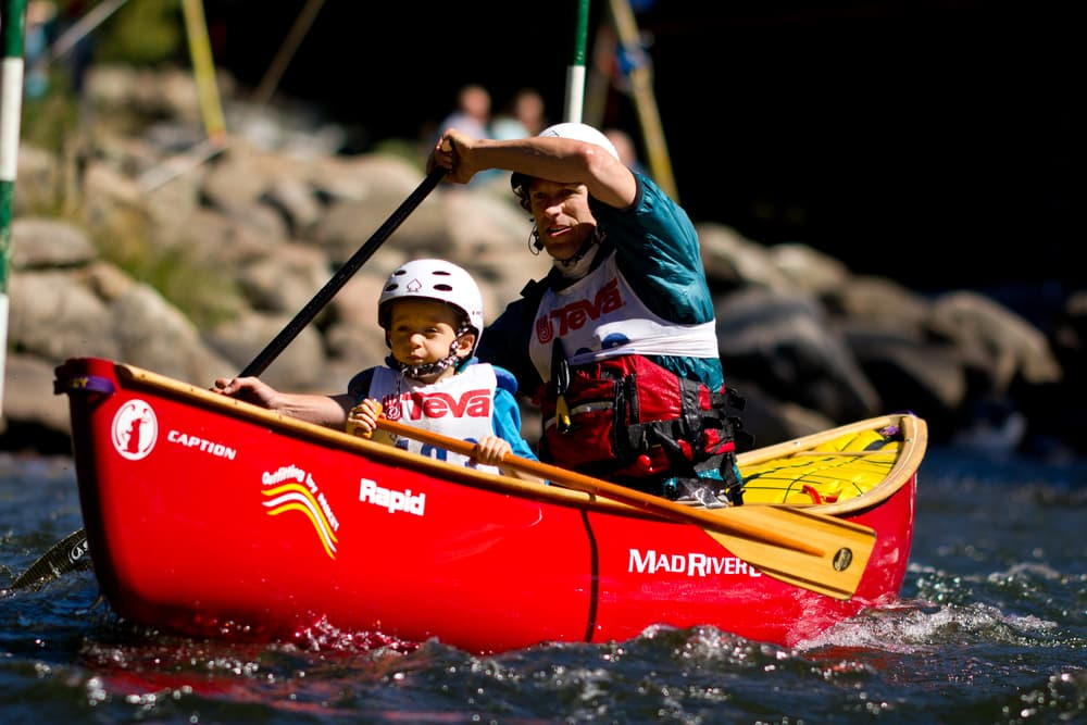 father and young child team paddling in a red canoe during an adventure race