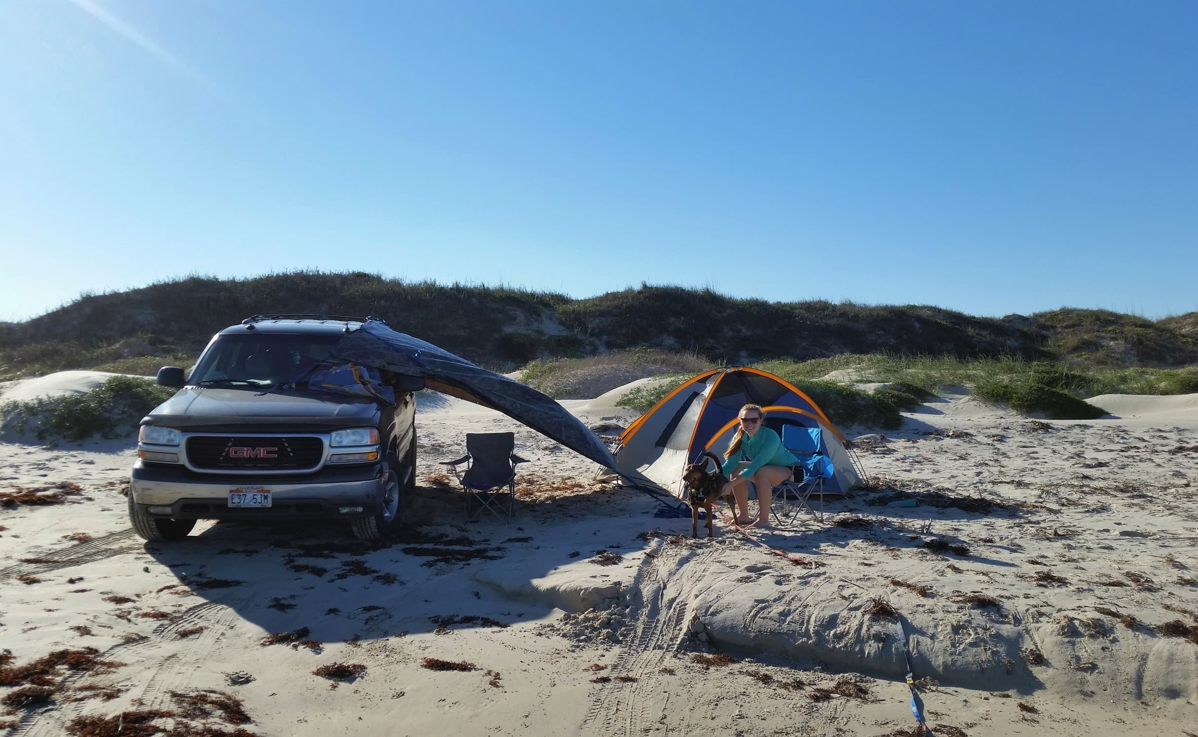 Woman sits with dog while camping on the beach with a tent and a sunshade made with a tarp and SUV