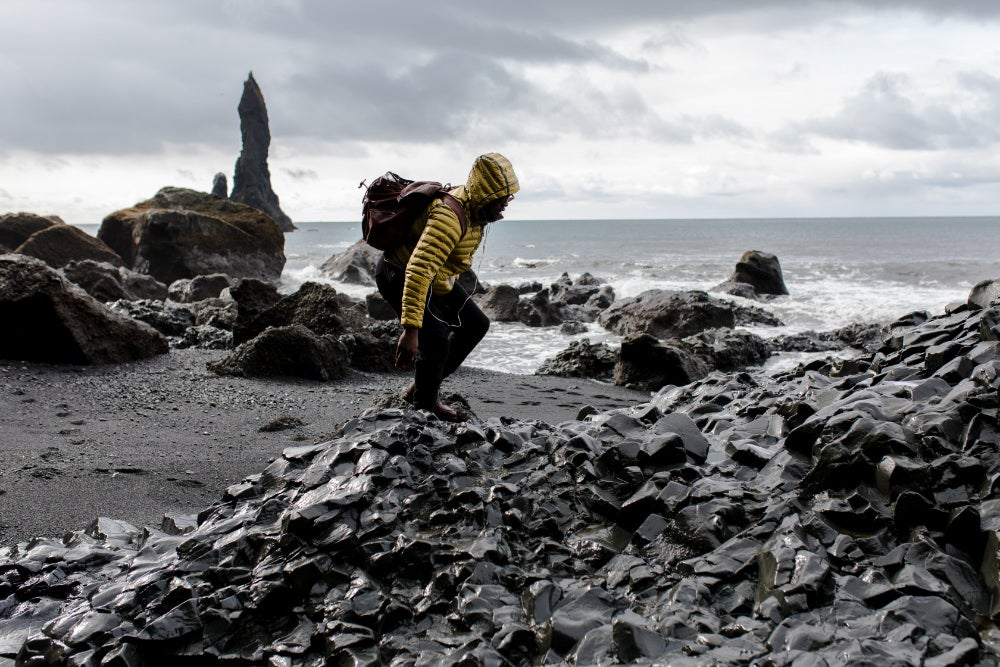 Man in yellow coat climbing on rocks at a black sand beach