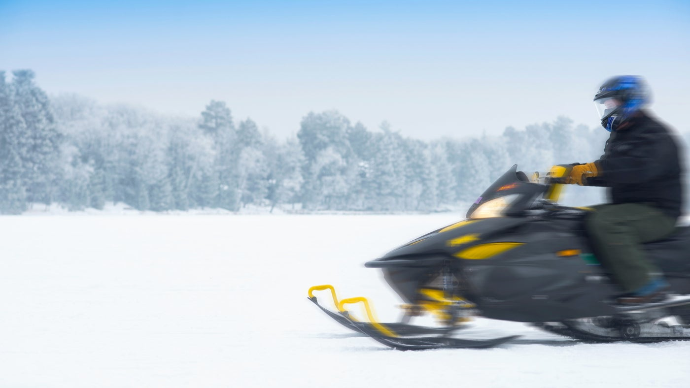 snowmobiler in motion riding beside snowy forest