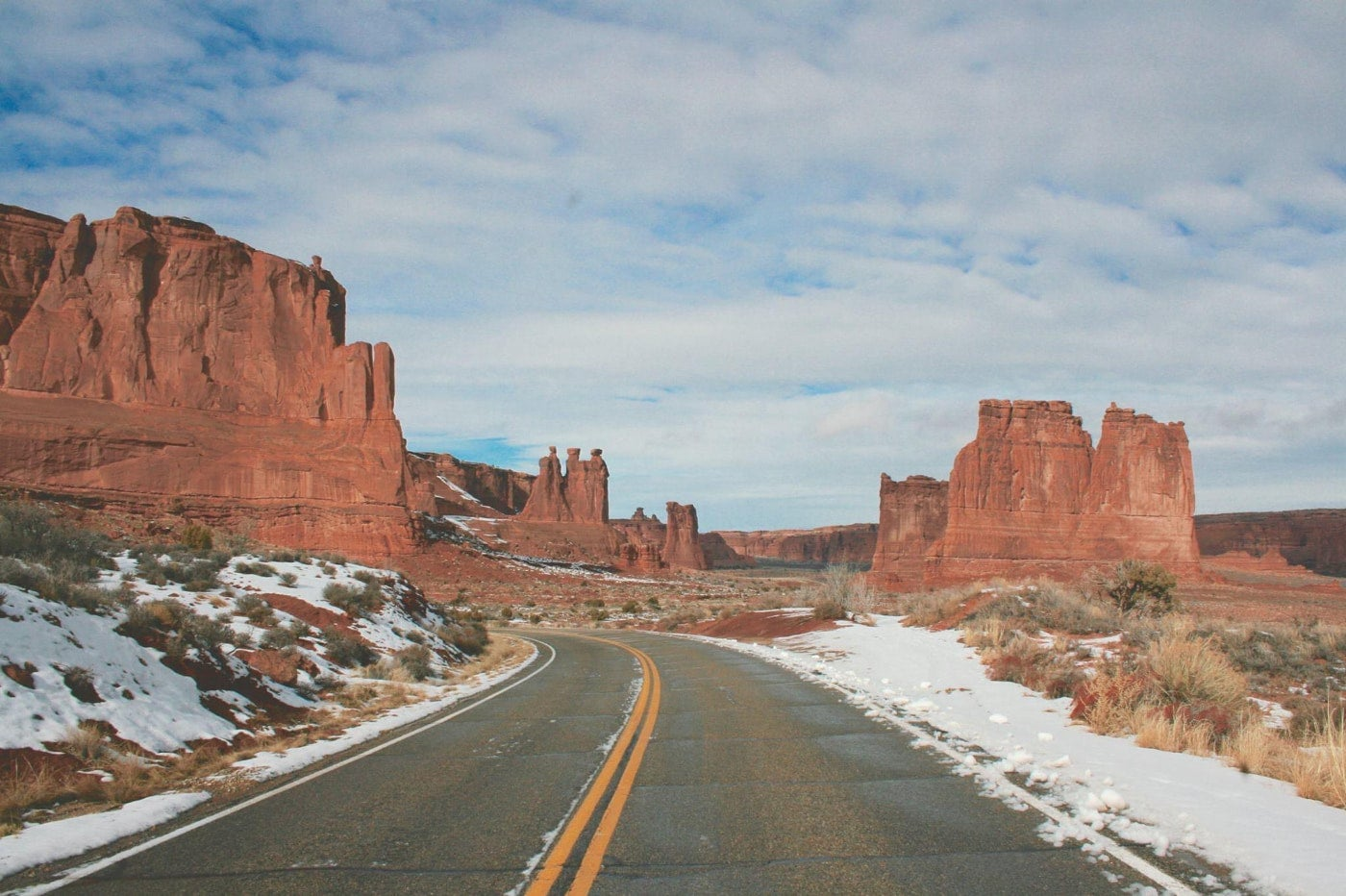 Two lane road winds through the snow-dusted desert in arches national park surrounded by red rock formations