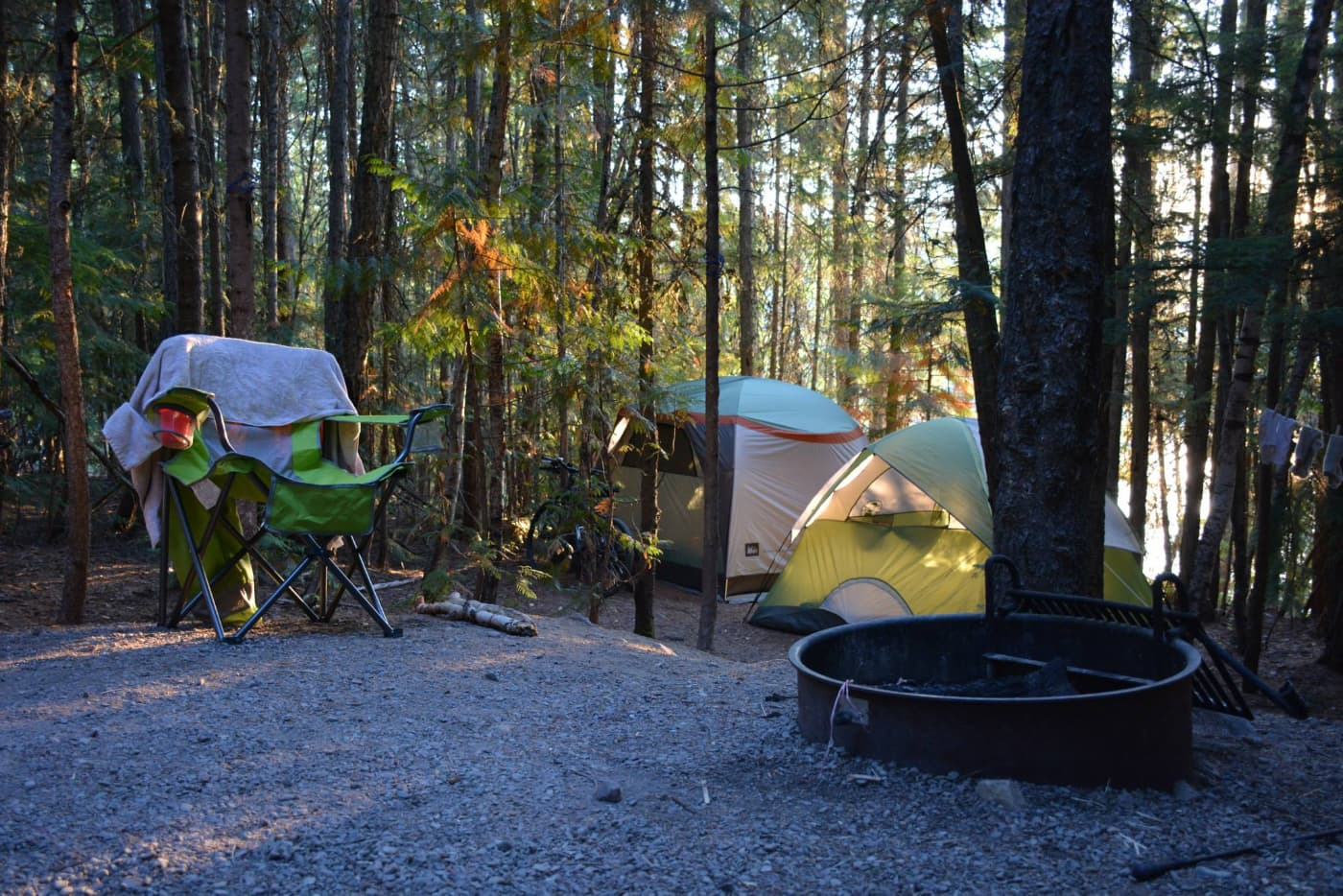 wooded campsite at fish creek campground with two tents and a camping chair behind a fire ring