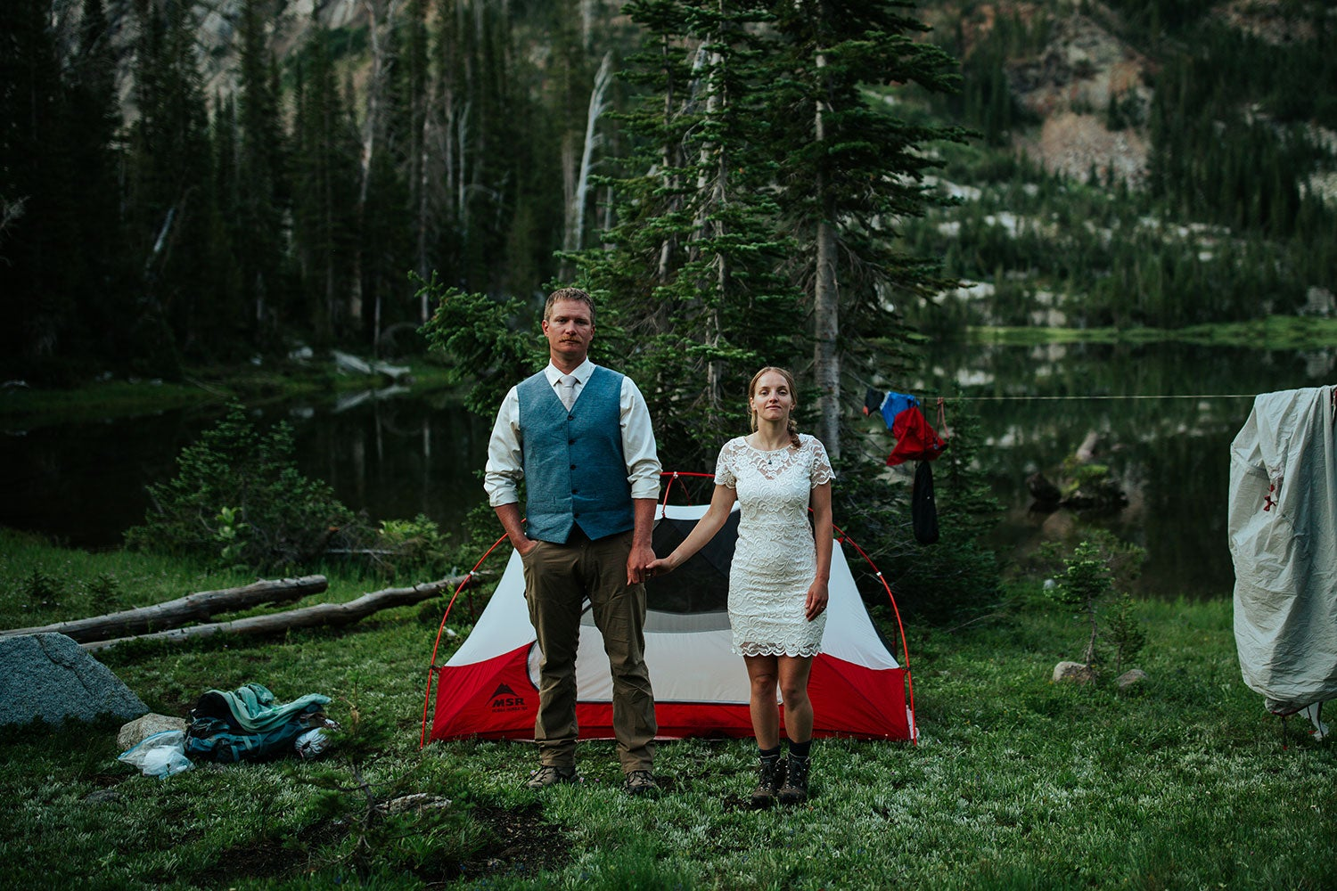 a man and a woman holding hands and wearing wedding attire at a campground in front of a tent on the edge of a forested lake