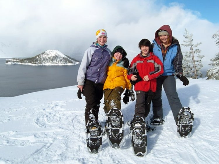Two women and two boys wearing snowshoes pose together in front of crater lake in the winter.