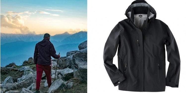a black rain jacket is seen worn by a man climbing a mountain with the hood tucked in, and also seen unworn with the hood up